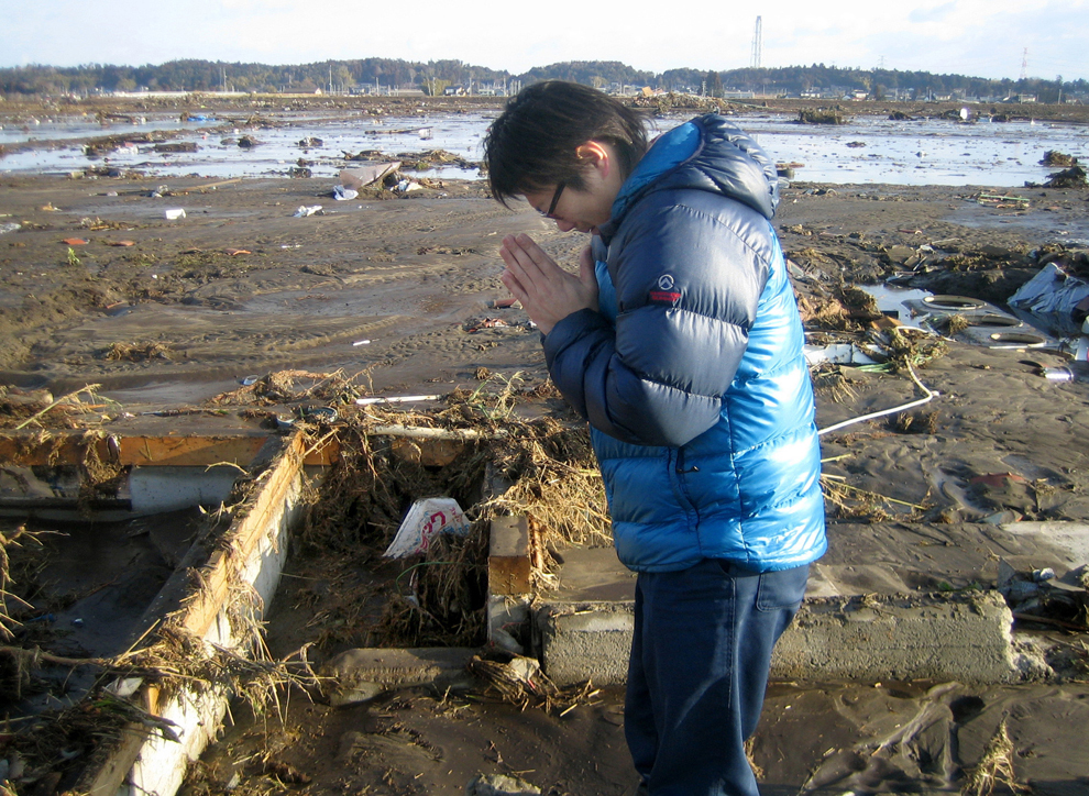 Japanese man praying after earthquake in Japan