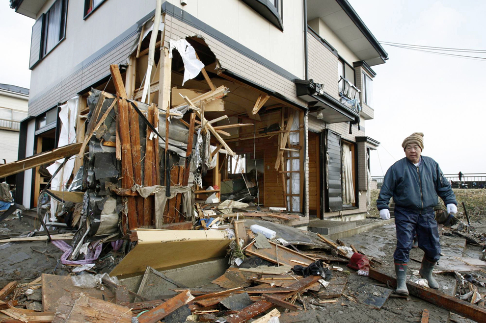 Japanese man working out of a house destroyed from the tsunami in Japan
