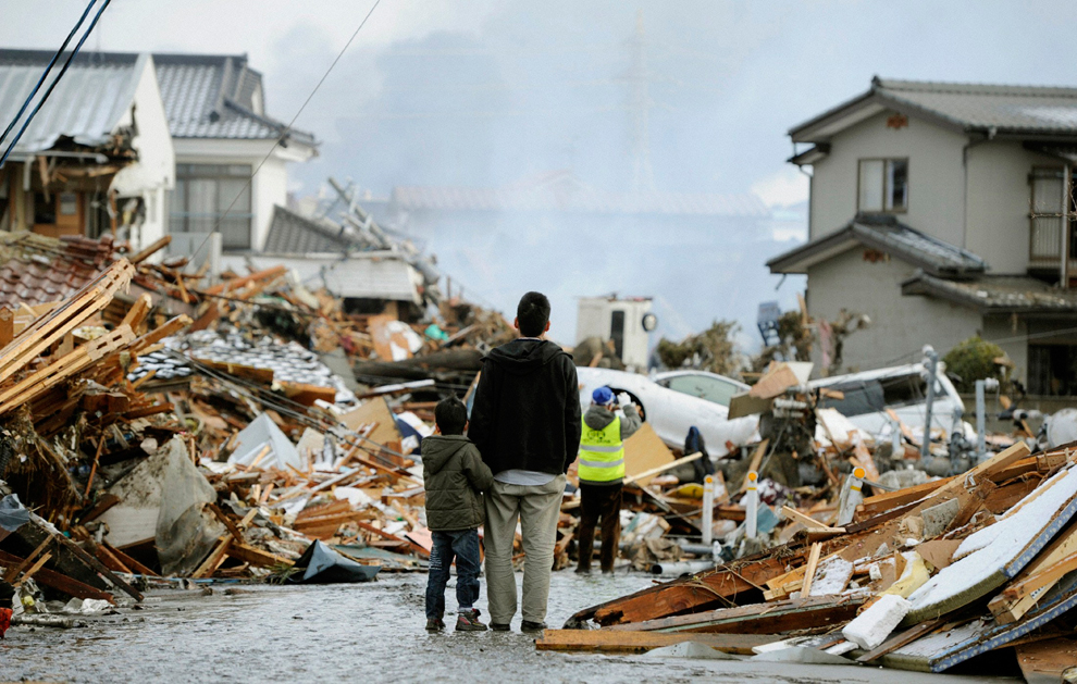 Japanese dad and son watching the rest of the houses destroyed after earthquake in Japan town