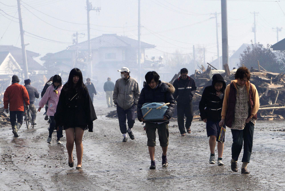 Japanese walking inside a town destroyed after earthquake in Japan