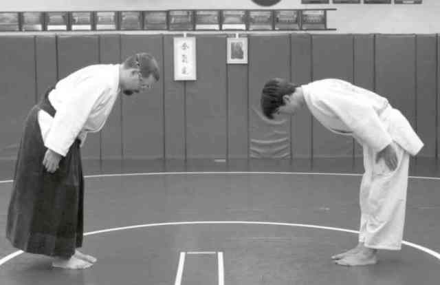 Two people bow in front of each other in martial arts